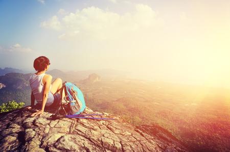 女性ハイカーが夕日の山ピークの崖で景色を楽しむ