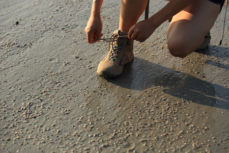 shoelace: woman hiker tying shoelace on sunrise beach