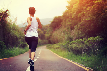 person outdoors: young fitness woman running at forest trail