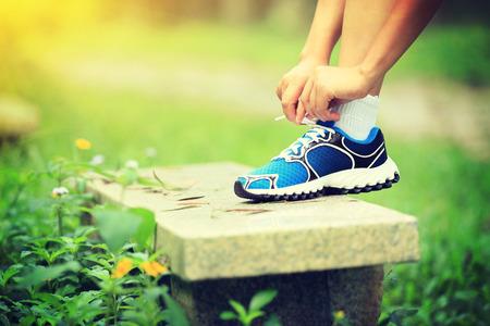 shoelace: woman tying shoelace outdoor