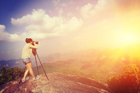 taking photo: young woman photographer taking photo on mountain peak