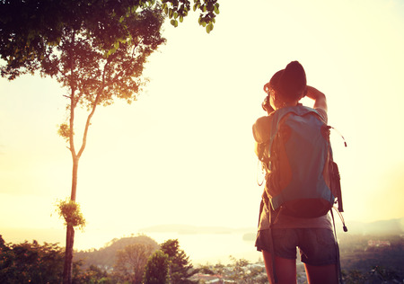 silueta humana: excursionista de joven toma fotos en el pico de la monta�a puesta de sol