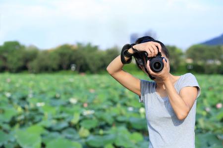 taking photo: woman photographer taking photo outodor Stock Photo