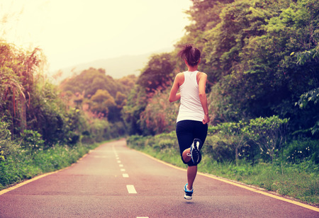 active: young fitness woman running at forest trail