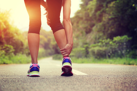deporte: Corredor de la mujer abrazarla deportes lesion� la pierna Foto de archivo