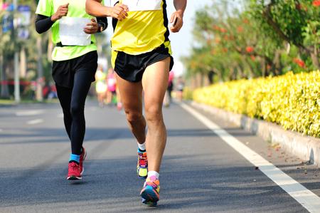 outdoor exercise: Marathon running race, people feet on city road Stock Photo