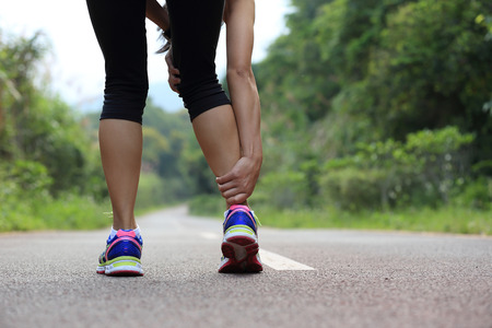 twitch: woman runner hold her sports injured leg