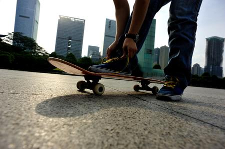 shoelace: skateboarder tying shoelace at skate park