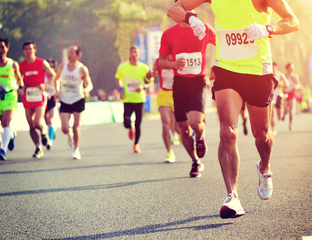 pies masculinos: Maratón de carrera a pie, la gente los pies en el camino de ciudad