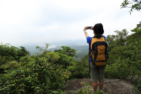 taking photo: woman hiker taking photo with cellphone at mountain peak cliff Stock Photo