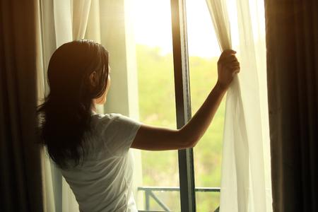 jonge vrouw opening gordijnen in een slaapkamer Stockfoto
