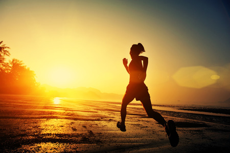 sunrise: young healthy lifestyle woman running at sunrise beach Stock Photo