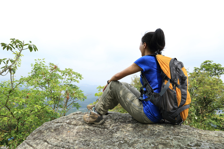 one young woman: woman hiker enjoy the view at sunset mountain peak cliff