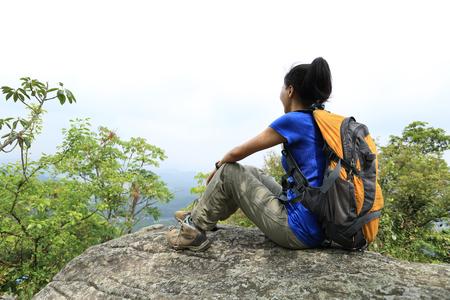 woman mountain: woman hiker enjoy the view at sunset mountain peak cliff