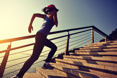 trails: healthy lifestyle sports woman running on stone stairs sunrise seaside