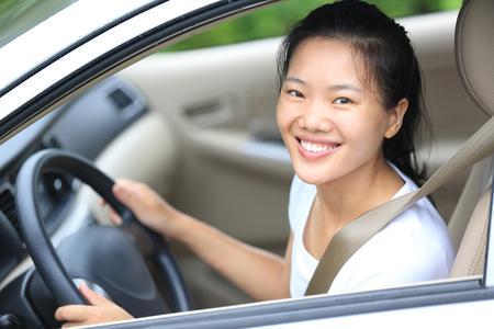 cheerful woman: conductor joven mujer asi�tica conducir un coche