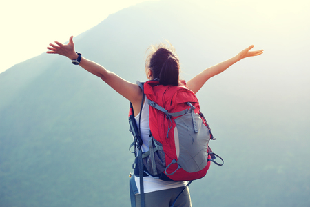 red mountain open space: young woman hiker open arms moutain peak Stock Photo