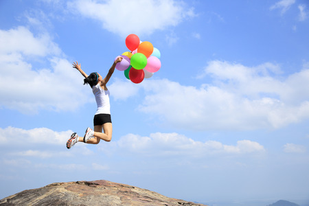 cliff jumping: young asian woman jumping on mountain peak rock with colored balloons