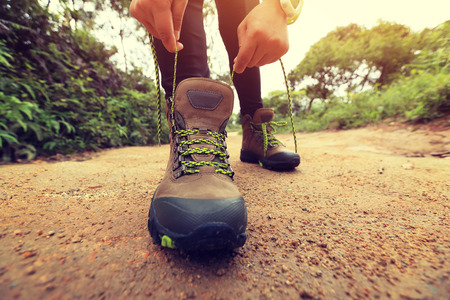 forest trail: woman hiking tying shoelace on forest trail