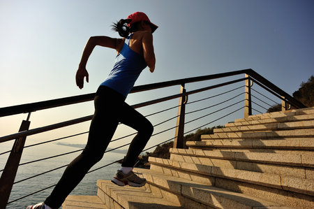 active lifestyle: healthy lifestyle sports woman running up on stone stairs seaside
