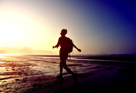 siluetas mujeres: excursiones mujer joven en la playa de la salida del sol Foto de archivo
