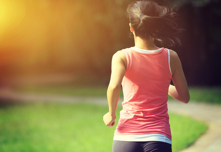 Runner athlete running at park trail. woman fitness jogging workout wellness concept.