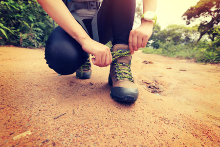woman outdoor: woman hiking tying shoelace on forest trail