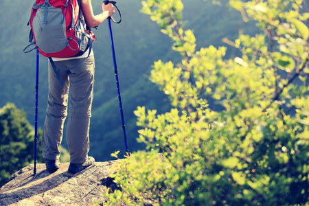ifestyle: woman hiker legs stand on mountain peak rock Stock Photo