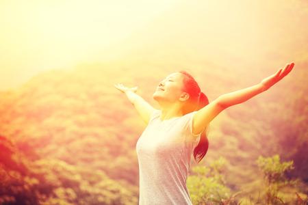 inspiración: mujer animando disfrutar de la hermosa vista al pico de la montaña