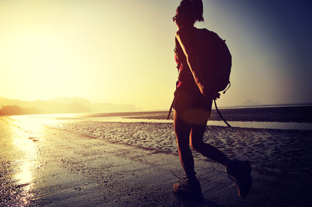 hiking: young woman hiking on sunrise beach Stock Photo
