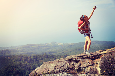 are taking: young woman hiker taking photo with smart phone at mountain peak