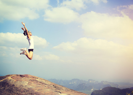 自由若いアジア女性山ピークの岩の上ジャンプ 写真素材