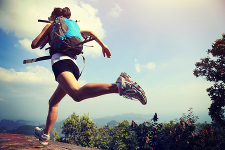 mountains and sky: young asian woman hiker running on mountain peak cliff Stock Photo