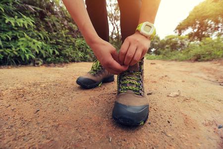 shoelace: hiker tying shoelace on trail