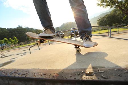 skateboard: skateboarder legs skateboarding at skatepark ramp