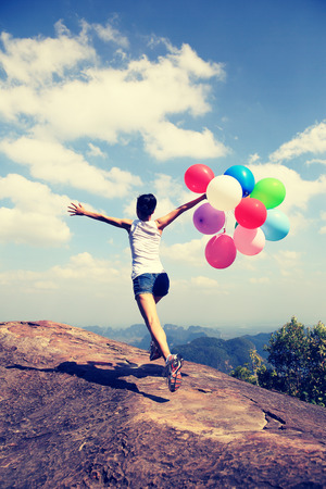 red mountain open space: young asian woman running on mountain peak rock with colored balloons
