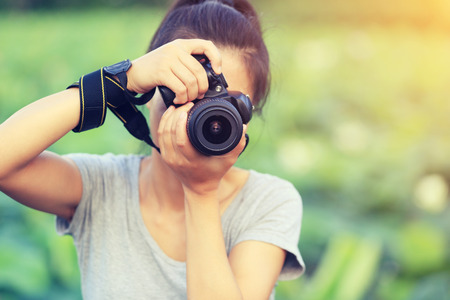 signle: young woman photographer taking photo outdoor Stock Photo