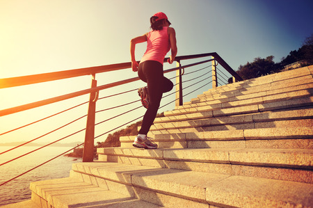 steps to success: healthy lifestyle sports woman running up on stone stairs seaside