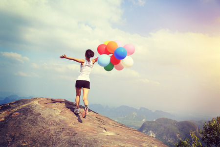 rock stone: young asian woman running on mountain peak rock with colored balloons