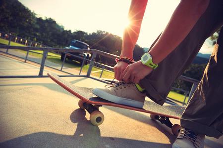 shoelace: skateboarder hands tying shoelace at skatepark