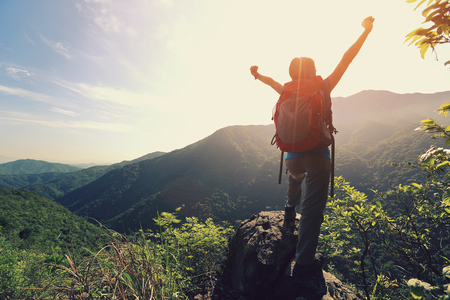 adventure travel: cheering woman hiker open arms at mountain peak Stock Photo