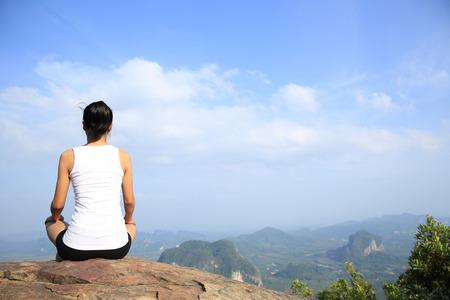 blue back: young yoga woman mountain peak