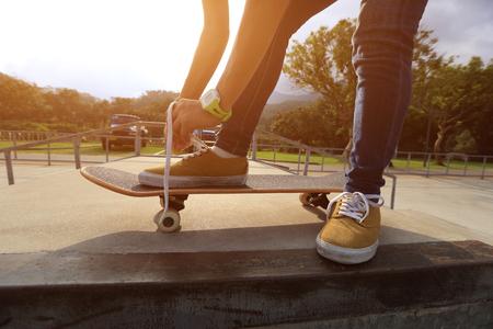 shoelace: skateboader hands tying shoelace on skateboard Stock Photo