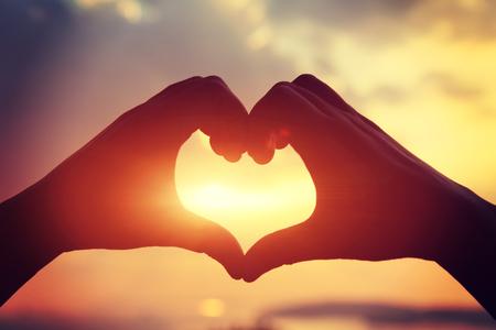 simbolo de la mujer: toma la forma del corazón de las manos contra la puesta de sol brillante mar y forma de oro de sol en el agua Foto de archivo