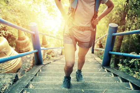 escalera: caminante de la mujer que sube las escaleras en la cima de la montaña