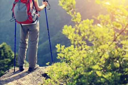woman hiker legs stand on mountain peak rock Stock Photo