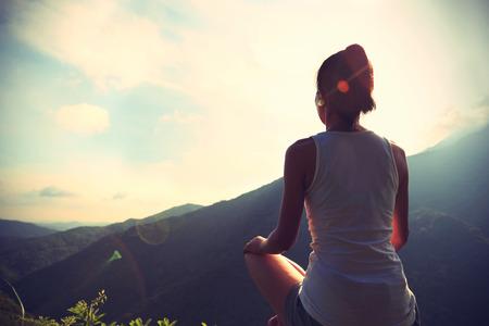 piedras zen: Yoga de la mujer joven en el pico de la monta�a la salida del sol