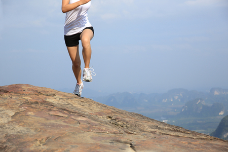 mountains and sky: young asian woman running on mountain peak cliff