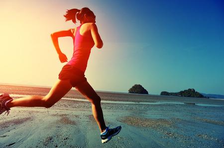 サンライズ ・ ビーチで走っている若い健康的なライフ スタイル女性