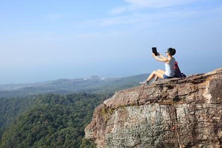 taking photo: woman hiker taking photo with digital tablet at mountain peak Stock Photo